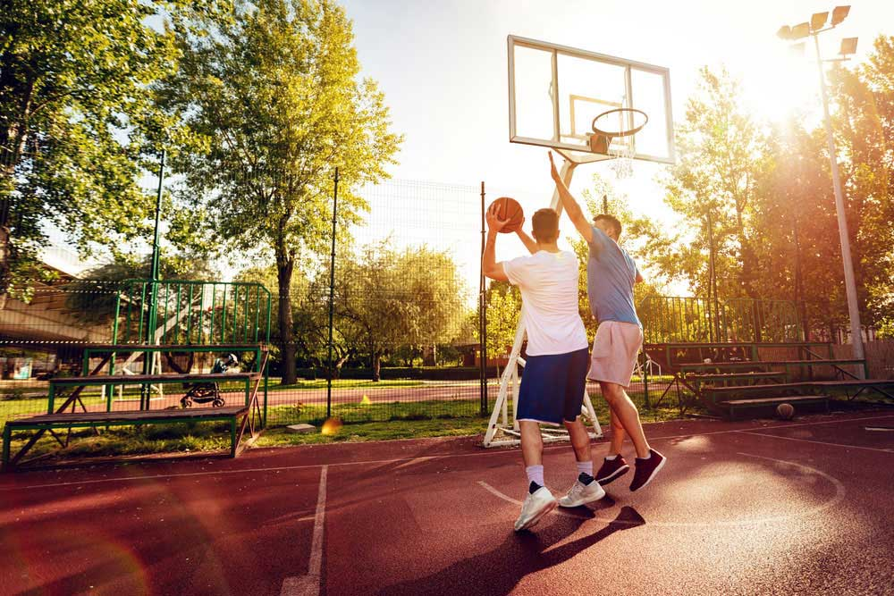 Two brothers playing basketball outside on a nice day