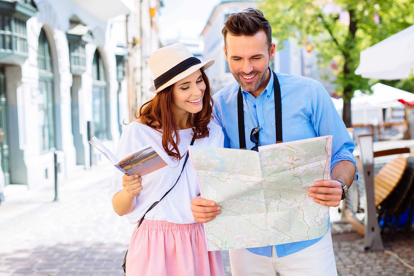 A couple on vacation in the summer looks at a map while practicing safe travel tips