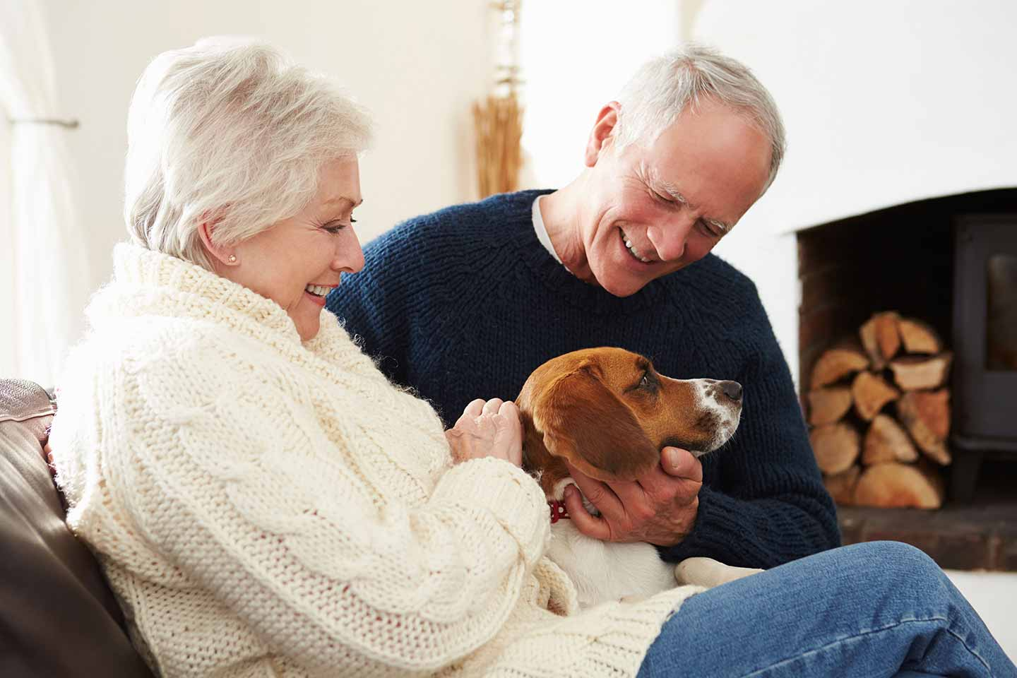 Couple in their sixties at home on the couch with their dog.