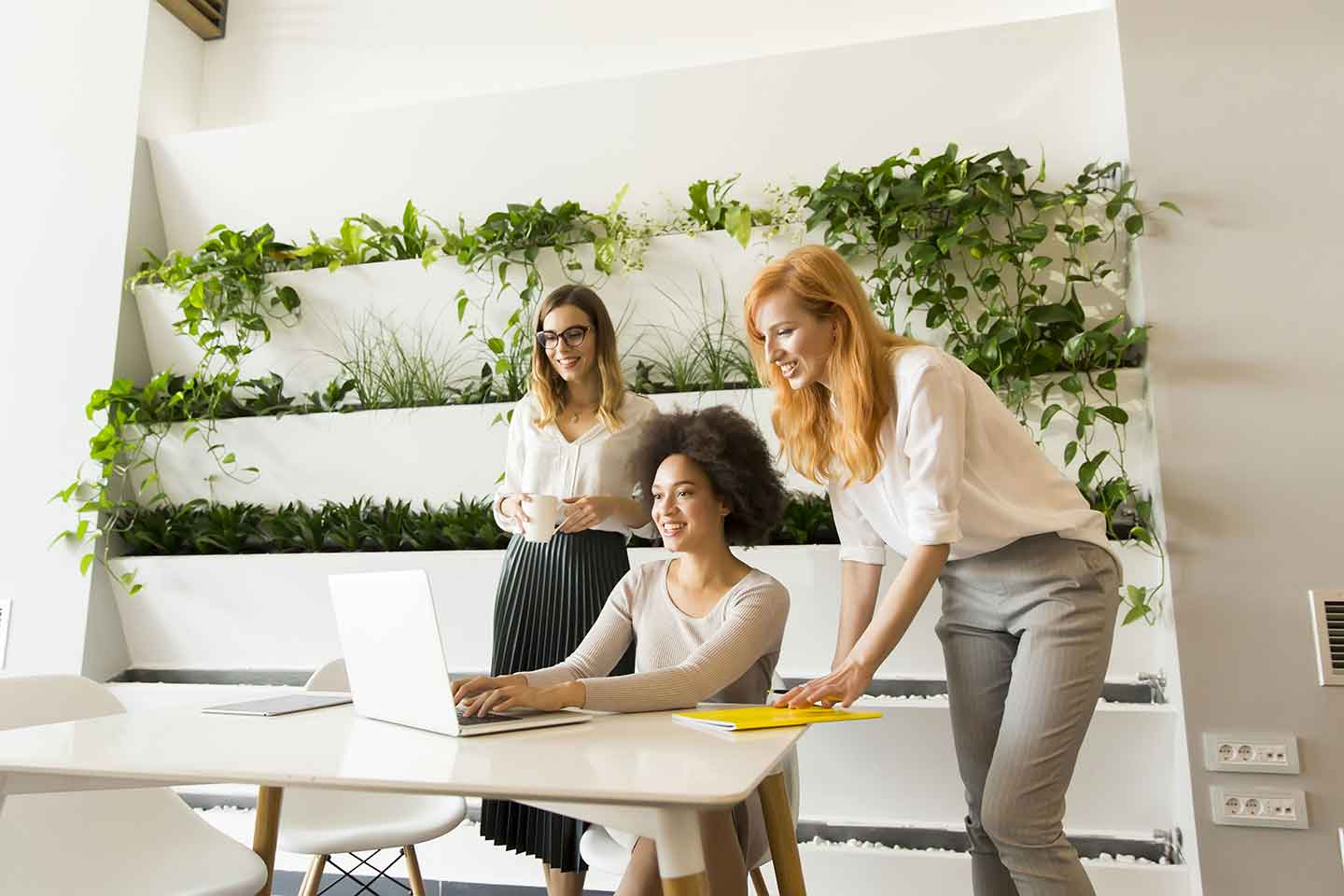 Group of three female entrepreneurs brainstorming sustainable business practices in an eco-friendly office.