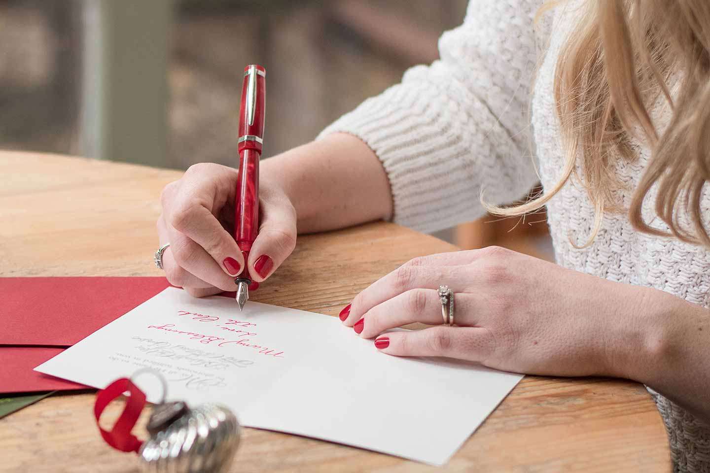 Women writing holiday cards to give with a financial gift.