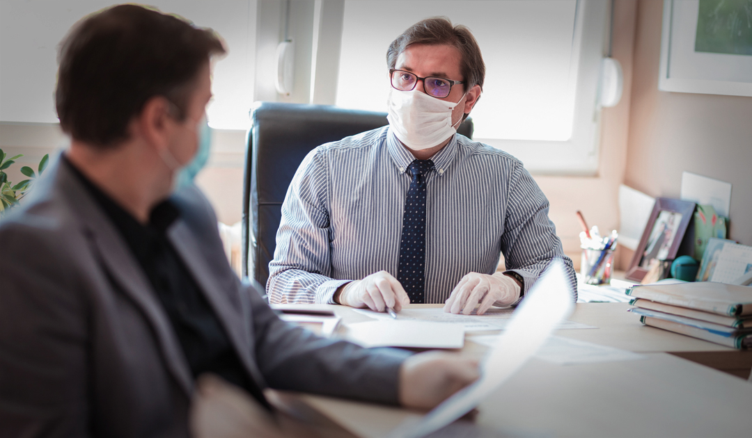 business man wearing pandemic mask at desk