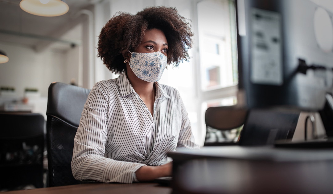 Office worker wearing mask at desk