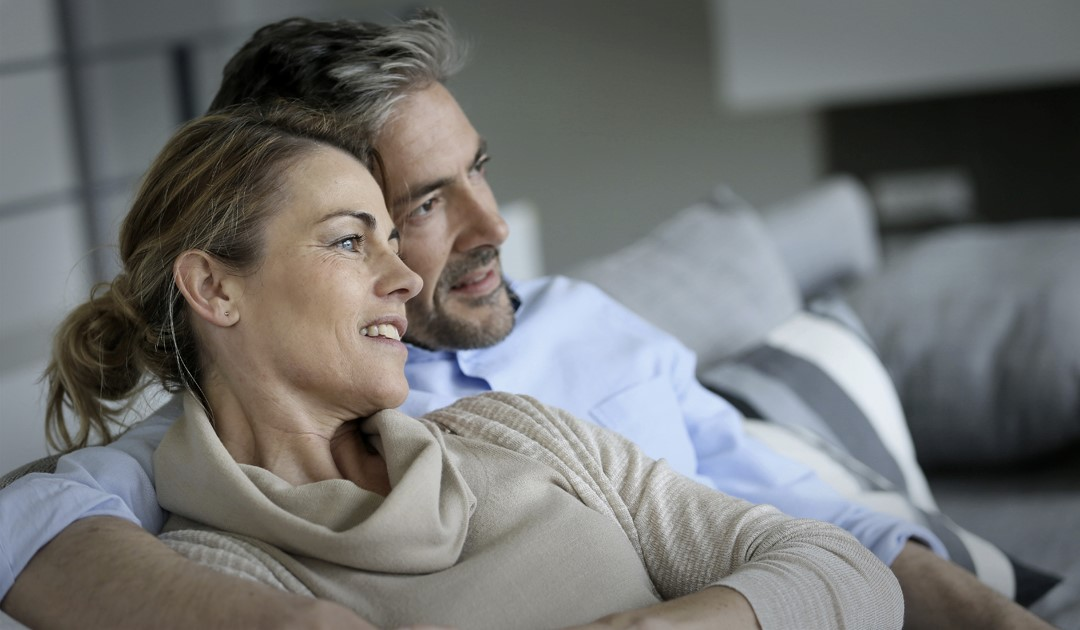Couple relaxes on the couch, thinking about their plans for their inheritance.